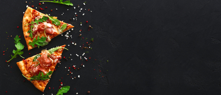 Fette di pizza con prosciutto e spezie su sfondo nero, copia spazio, vista dall'alto