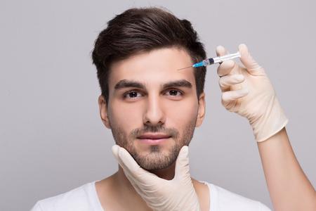 Iniezione di riempimento sulla fronte per viso maschile in clinica di bellezza Archivio Fotografico