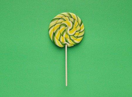 Top view on large spiral lollipop on green background 写真素材