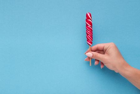 Female hand suggesting lollipop. Fun concept, copy space on blue