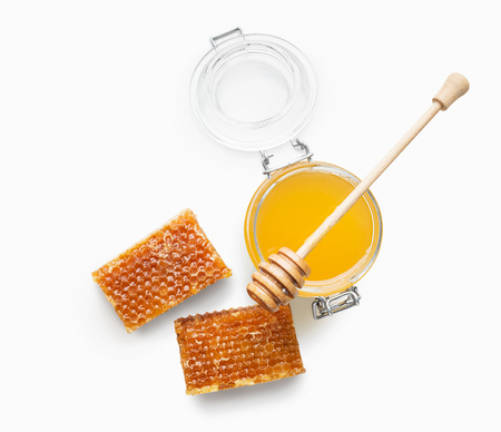 Jar full of fresh honey with wooden dipper and honeycombs isolated on white background, top view Banque d'images
