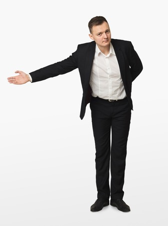 Young businessman in suit bowing and gesturing welcome, isolated on white background