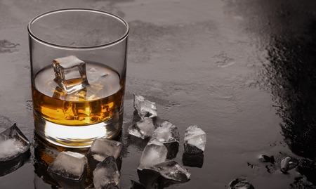 Portion of cold whiskey with ice cubes on black background, copy space