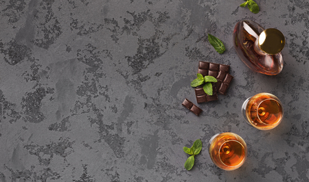 Delicious break at business meeting. Two glasses with cognac, bottle and chocolate on marble background, copy space