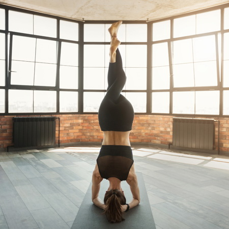 Fit woman in upside down position with interweaved legs, professional athlete doing headstand balance exercise, copy space