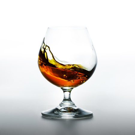 Brandy splash in glass on white background
