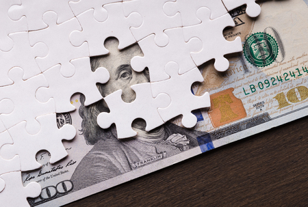 Hidden assets concept. One hundred dollar banknote appearing under puzzle pieces