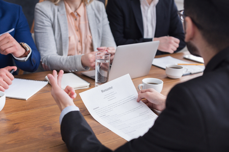 Commission interviewing young male job seeker for business in office