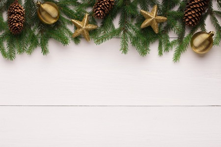 Christmas fir tree with golden stars and pine cones decoration on white wooden table, top view, copy space Banco de Imagens