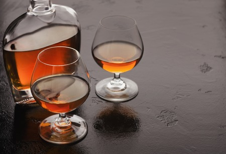 Evening aperitif. Two glasses of brandy or cognac and bottle on black background, copy space Banco de Imagens