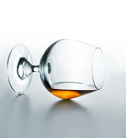 Cognac glass lies on its side with remains of brandy inside