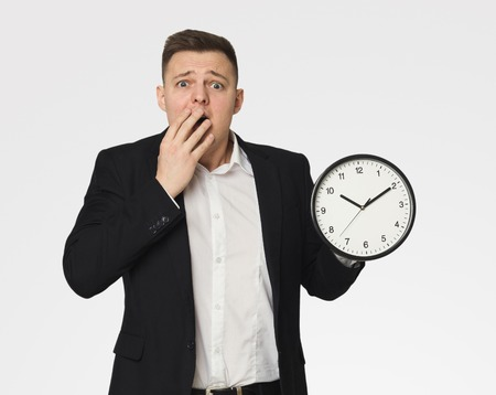 Late for business meeting, shocked man in suit holding clock, time management concept