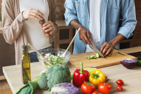 Black couple preparing healthy vegetable salad together in loft kitchen