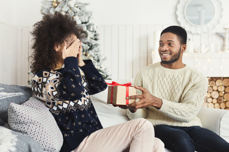 Surprise on Christmas. Happy man surprising his girlfriend with xmas gift, excited woman closing her eyes, copy space