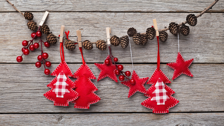 Christmas and New Year decorations made of felt are hanging on stick with pinecones, rustic wooden background, copy space Фото со стока