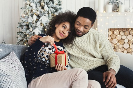 Winter holiday and love. Happy african-american couple celebrating Christmas at home, copy space Banco de Imagens