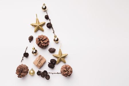 Kerstboom gemaakt van gouden sterren en kegels op witte achtergrond Stockfoto