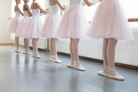 Young ballerinas in basic position. Ballet dancers standing near ballet barre