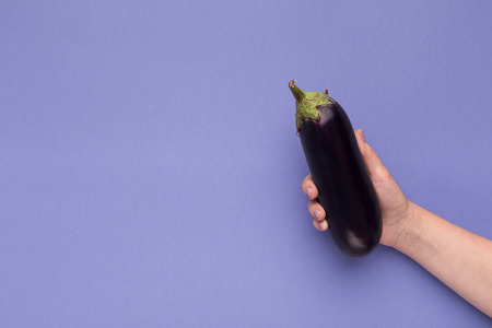 Female hand holding fresh ripe eggplant on purple background, copy space
