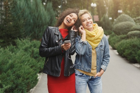 Happy multiethnic female friends listening to music on smartphone, sharing ear buds and singing while having a walk in city park. Leisure, technology, friendship and urban lifestyle concept 版權商用圖片