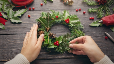 Female hands make Christmas wreath on dark wooden background