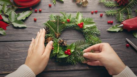 Vrouwelijke handen maken de kroon van Kerstmis op donkere houten achtergrond Stockfoto