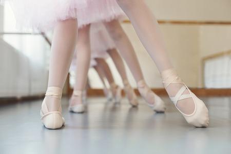 Group of little ballerinas training leg position at ballet class, copy space.