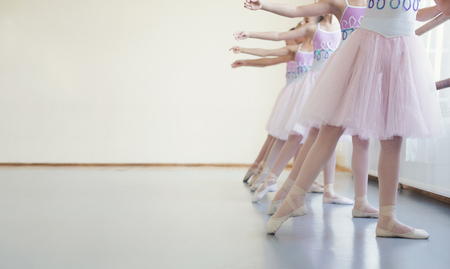 Little ballerinas stretching tiptoes in ballet class, copy space