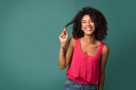 Happy african-american woman touching her curly hair over turquoise background
