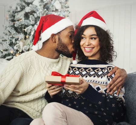 Young black man giving her girlfriend new year present and kissing her cheek