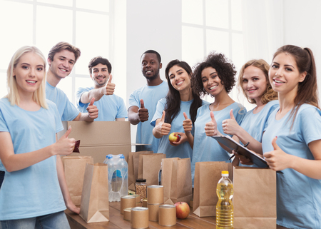 Group of volunteer showing thumbs up and smiling at camera, while packing food in office, copy space
