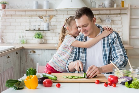 I love you, daddy. Pretty girl hugging dad while man cooking healthy dinner, copy space