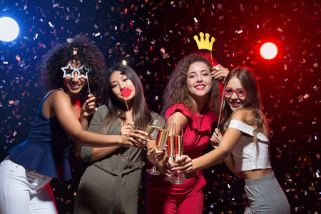 Fun at New Year party. Happy women celebrating and posing with photo props and champagne