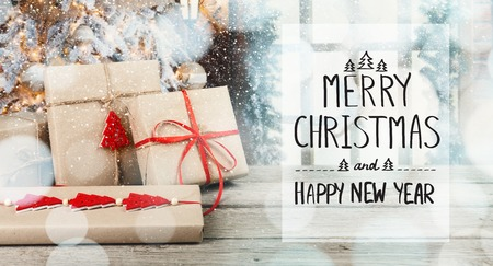 Merry Christmas and Happy New Year greeting card decorated with gift boxes in white bokeh background