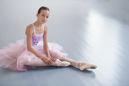 Enjoy your relaxation. Young ballerina sitting on floor in modern dancing studio, copy space Banque d'images