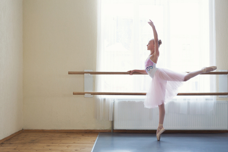 Young ballerina stretching at ballet barre in studio, copy space