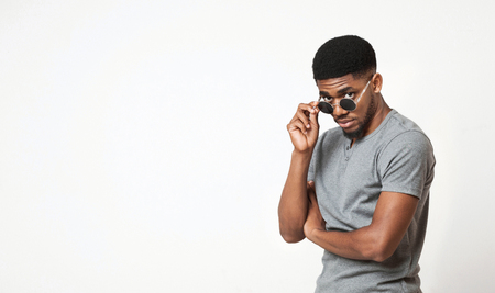 Handsome african-american man adjusting his sunglasses and looking at camera, white studio background, copy space