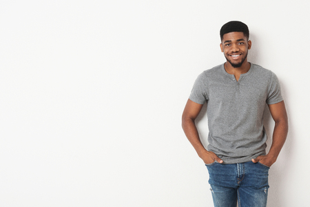 Young african-american casual man with his hands in his pockets, smiling to camera, white studio background with copy space Imagens
