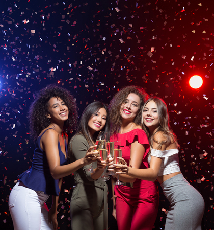 Happy New Year greeting card. Four happy diverse women congratulating you with champagne flutes, copy space Stock Photo