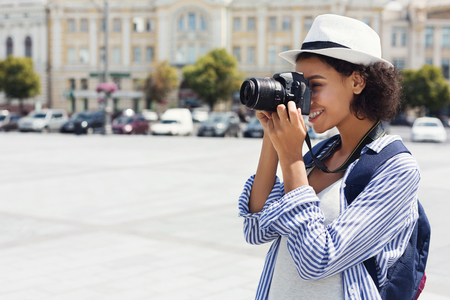 African-american woman photographing with camera on vacation in city