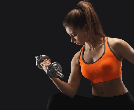 Athletic young woman with dumbbell on a black background.