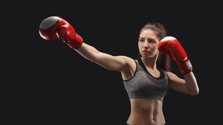 Gorgeous young woman with boxing gloves, standing in the defending position, ready to fight, copy space.