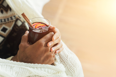 Man covered with plaid drinking hot red mulled wine with spices Stock Photo