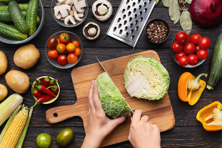 Female hands chopping savoy cabbage on wooden board, kitchen table with vegetables assortment, top view
