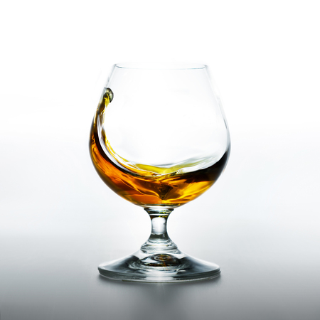 Glass with splashes of brandy on white