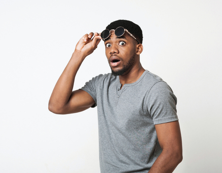 Surprised and shocked african-american man taking off his glasses in amazement