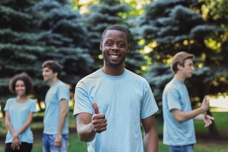 Cheerful african-american volunteer showing thumb up and smiling at camera, copy space