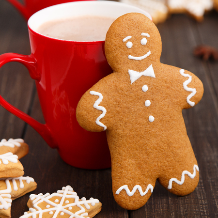 Gingerbread man leaning against red cup with cocoa Фото со стока