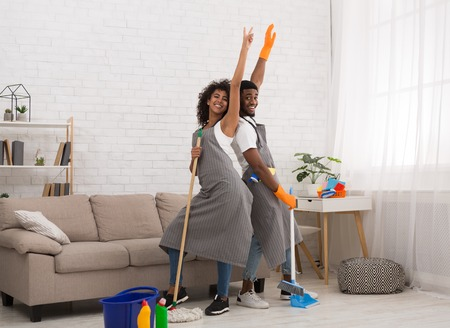African-american couple staring like on scene while cleaning home with mop and broom 版權商用圖片