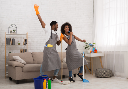 African-american man and woman cleaning apartment and having fun, staring like rockstars